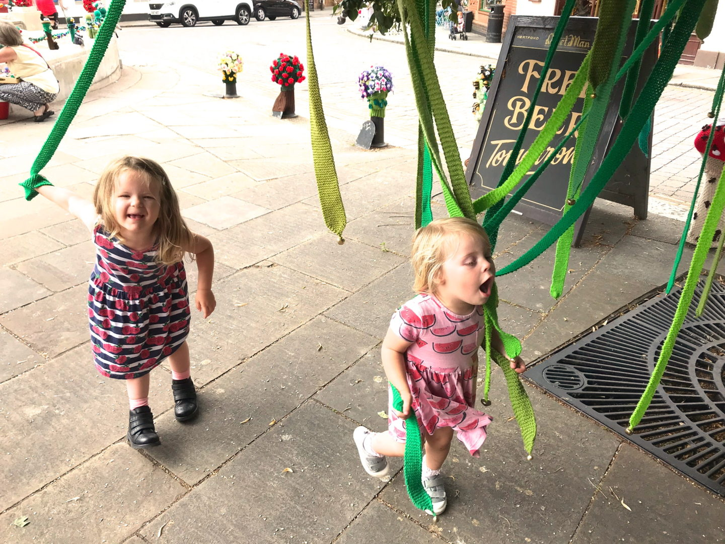 two little sisters exploring Hertford's Yarn Bombers' Enchanted Forest