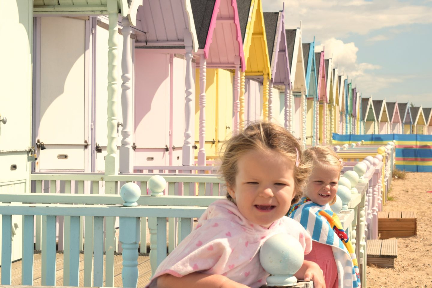 two little sisters on the decking of a beach hut, leaning on the balustrade