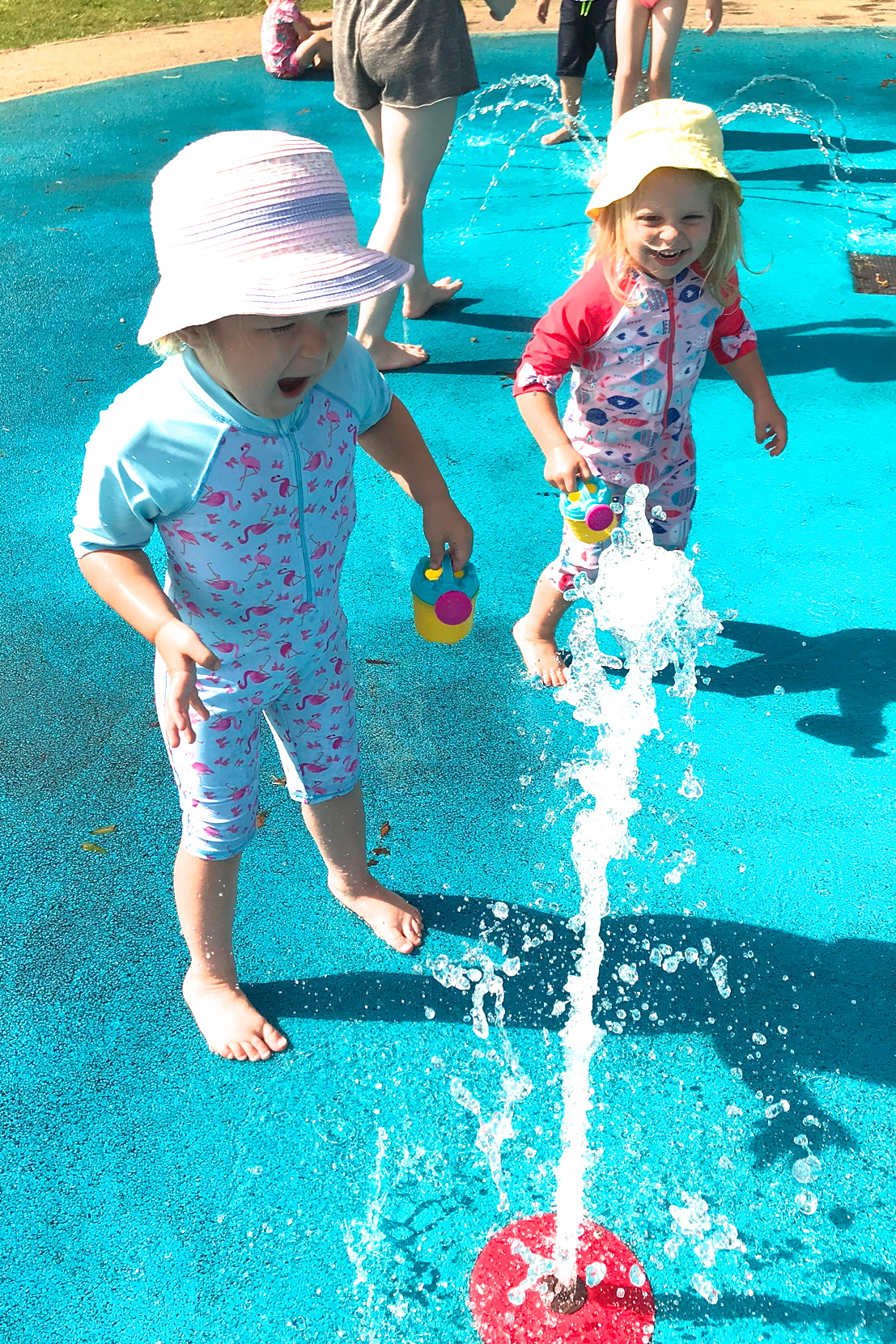 Two sisters in a splash park, playing with a jet of water, laughing