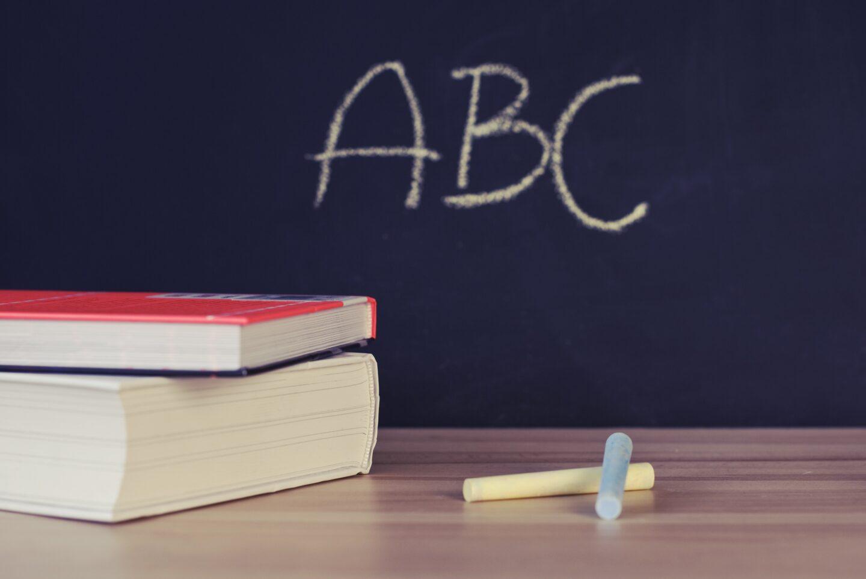 Blackboard showing ABC written in chalk with books on a desk