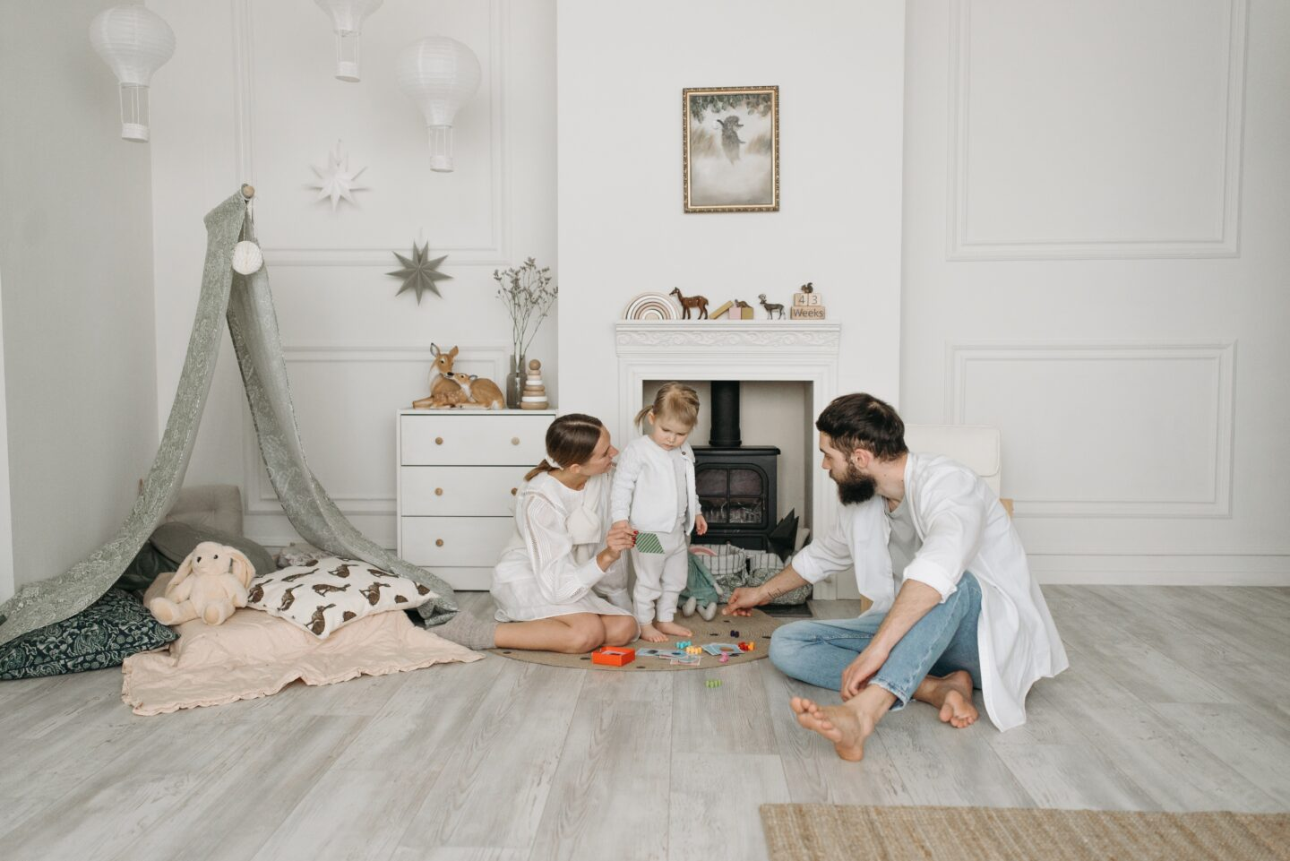 Family of three playing on the floor of a child's bedroom with teepee in the background
