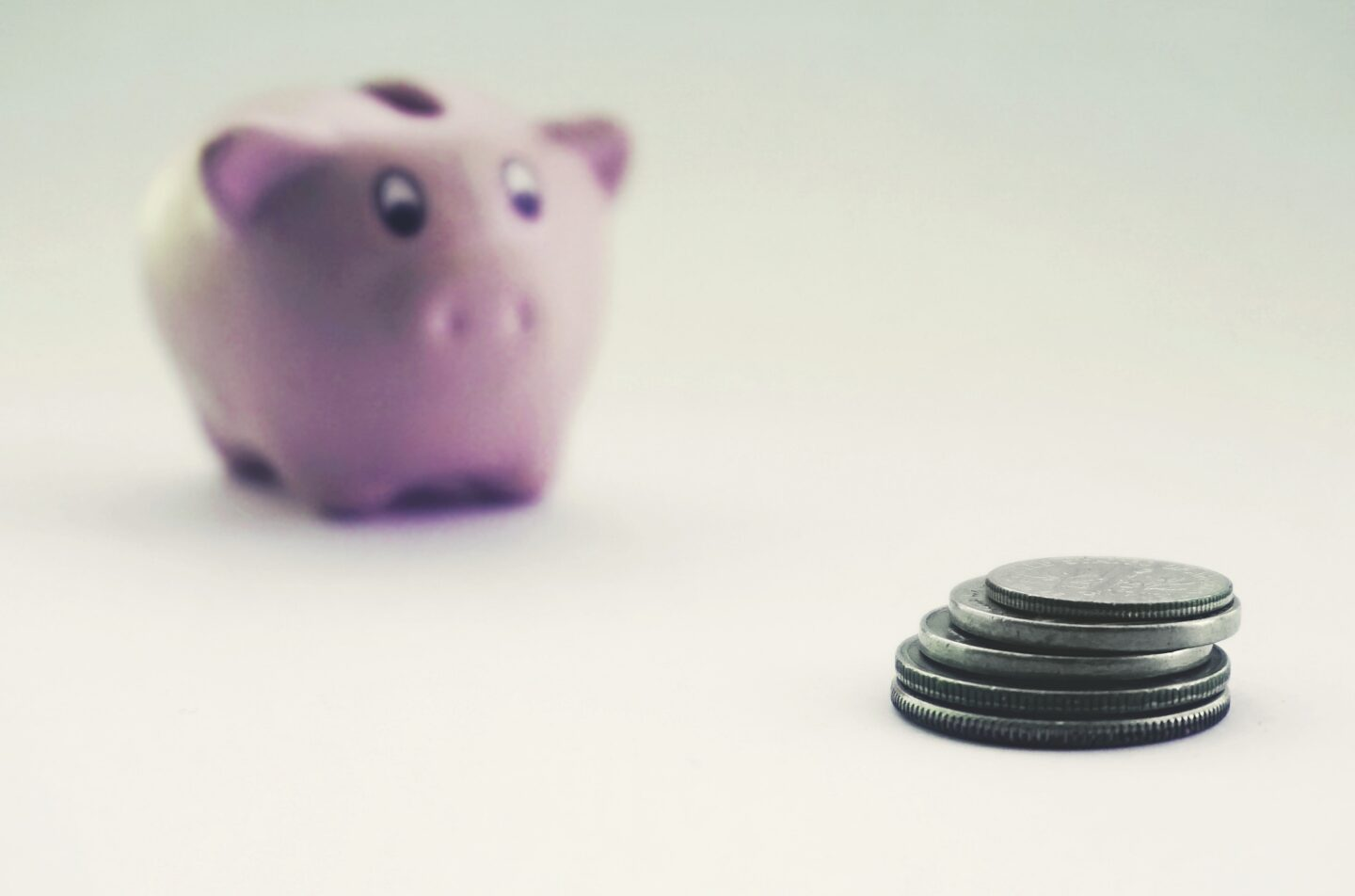 Piggy bank with money piled in front of it