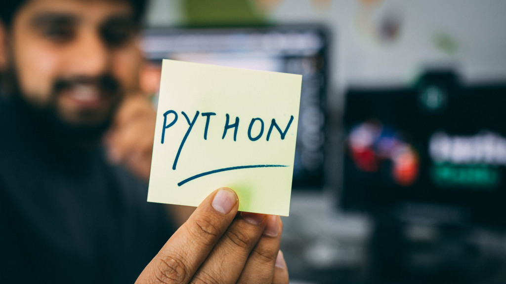 A man holding a post it note with the word Python written on, a common programming language.