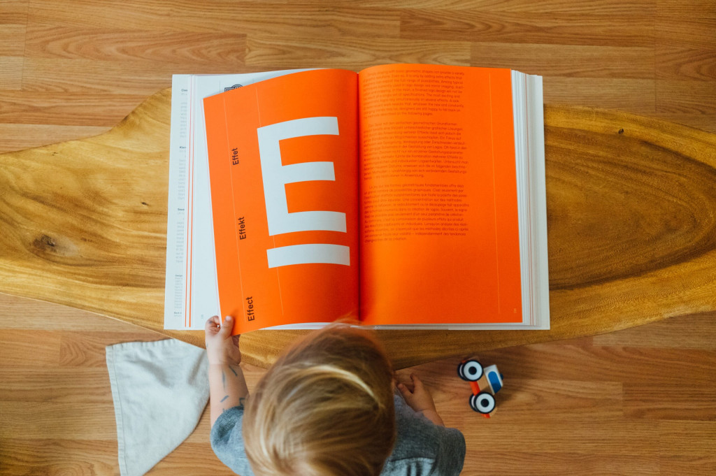 A child sat on the floor reading an orange book with a large letter E