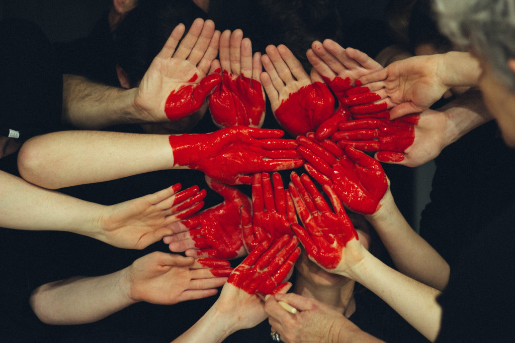 Painted hands together to form a red heart