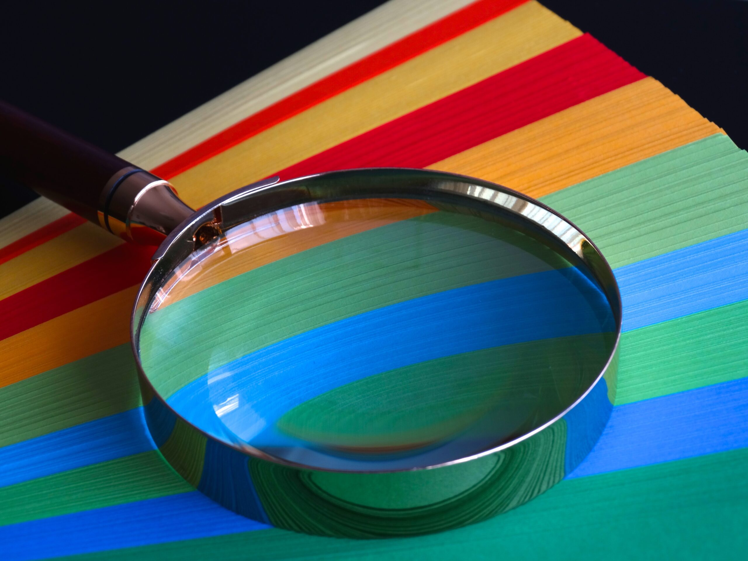 Magnifying glass over coloured paper - Rachel Writes proofreading service
