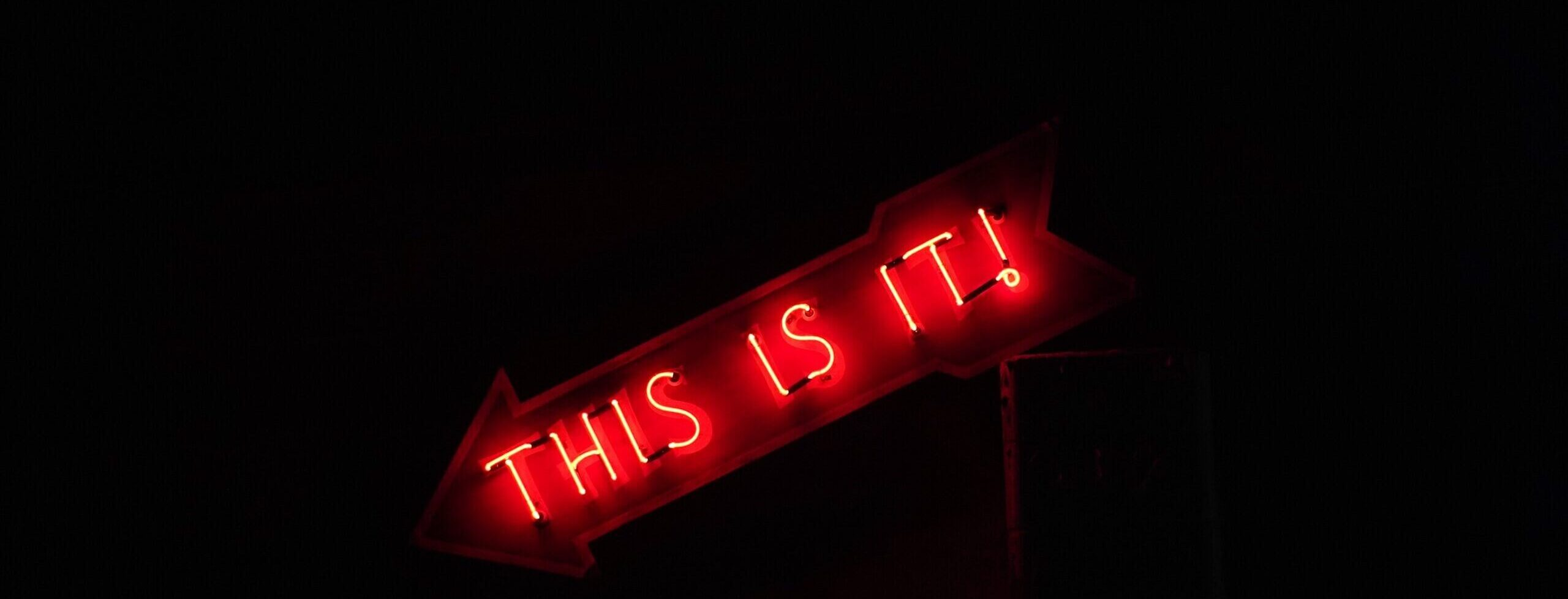 Neon sign reading 'This Is It!' - cropped - Rachel Writes email and e-newsletter writing service