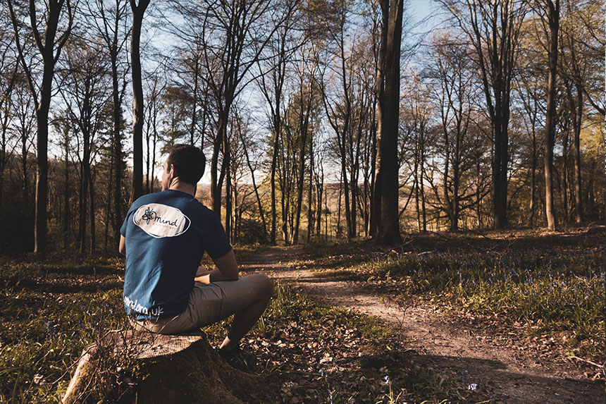 Tom sits on a tree stump in the woods wearing his charity Mind T-Shirt. Mind is a mental health charity.