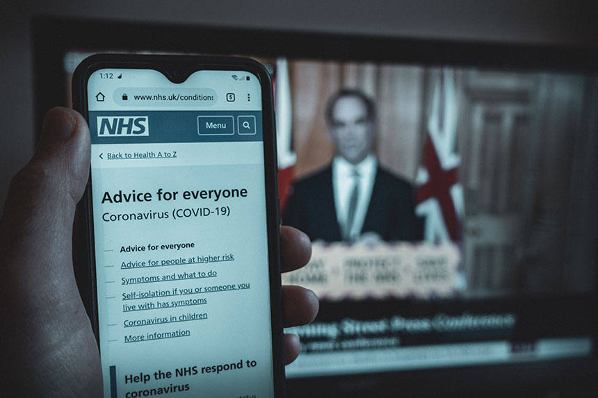 A hand holding a phone showing the NHS Covid-19 advice web page, with a tv in the background showing the BBC news Coronavirus update
