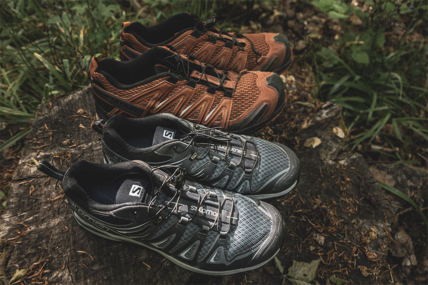 2 pairs of male and female salomon hiking shoes on a log