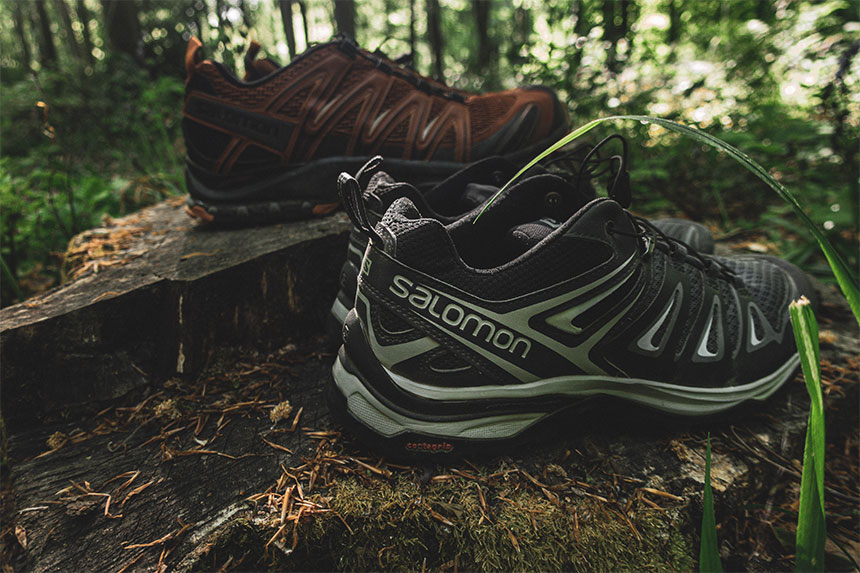 Profile of two pairs of Salomon hiking shoes on a log.