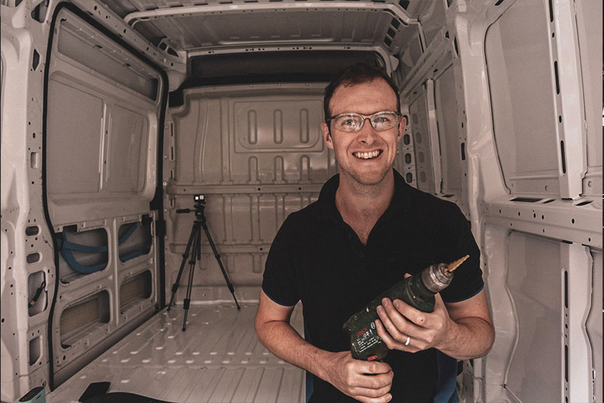 Tom holding a drill when removing rivits from the van walls
