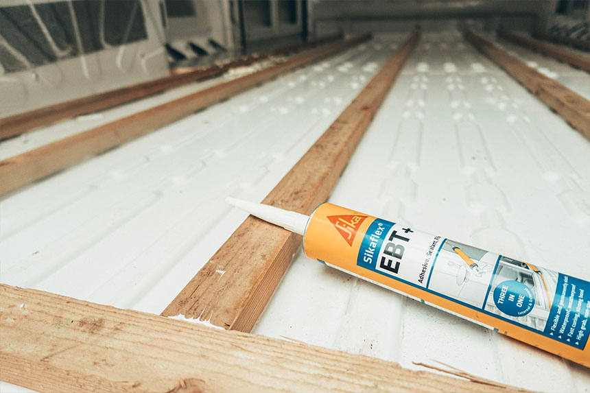 A tube of Sikaflex adhesive lying on the floor and on a recently glued wooden batten