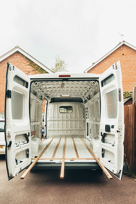View through back of the van doors of the wooden battens being laid out on the van floor