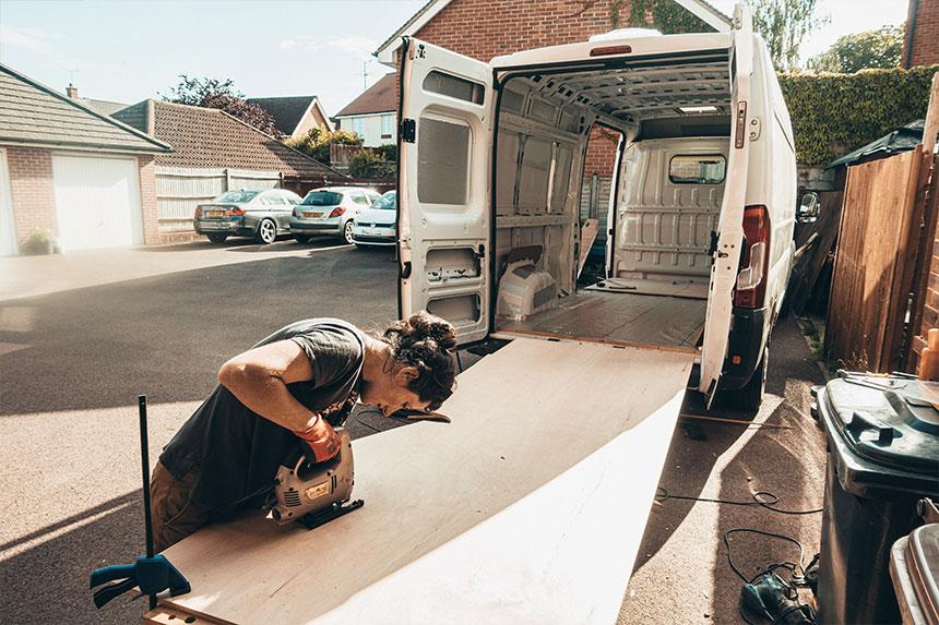 Max using a jigsaw to cut out a template for the new plywood van floor