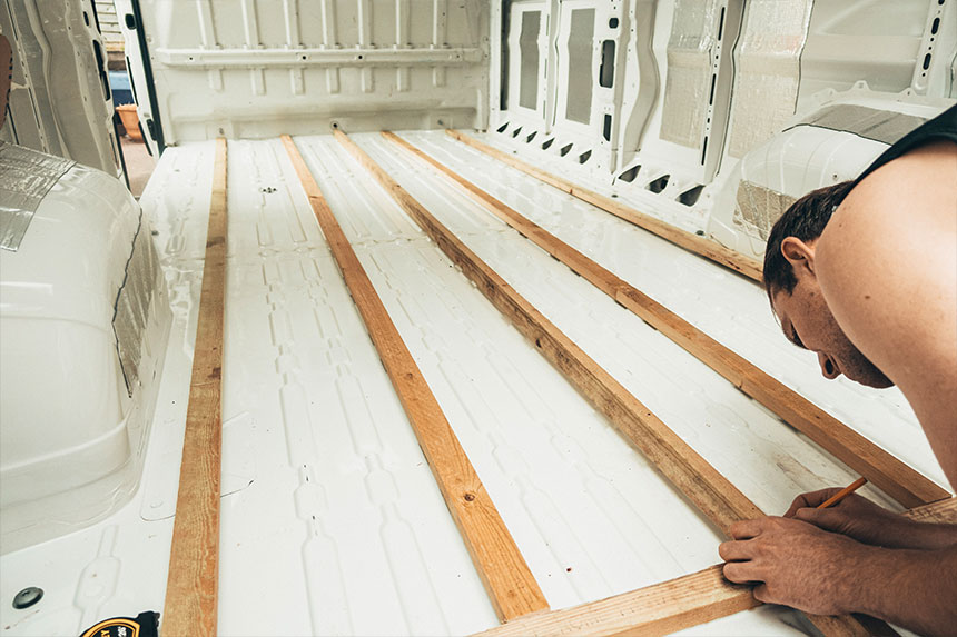 Tom marking out measurements on a wooden batten for the floor