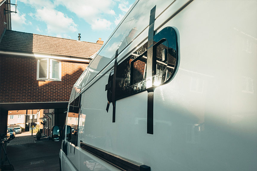 The van windows fitted with duct tape to hold them in place while the adhesive sets