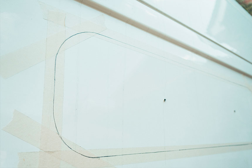 The area to cut the small slider van window out marked out on masking tape