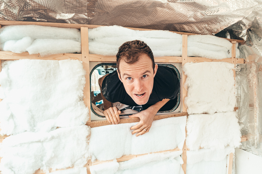 Tom sticks his head through the bulkhead hole amongst the van insulation and vapour barrier above him.