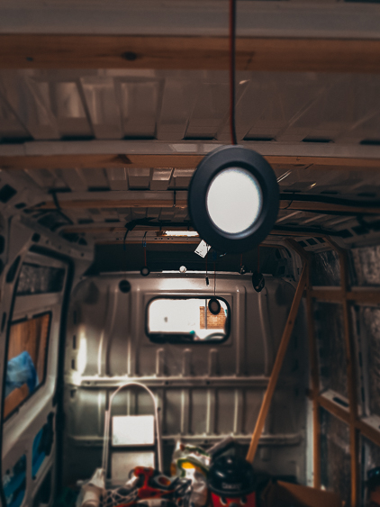 A small downlight hangs down from the ceiling ready to be tested in a dark van