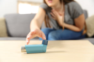 Girl suffering asthma attack reaching inhaler sitting on a couch in the living room at home