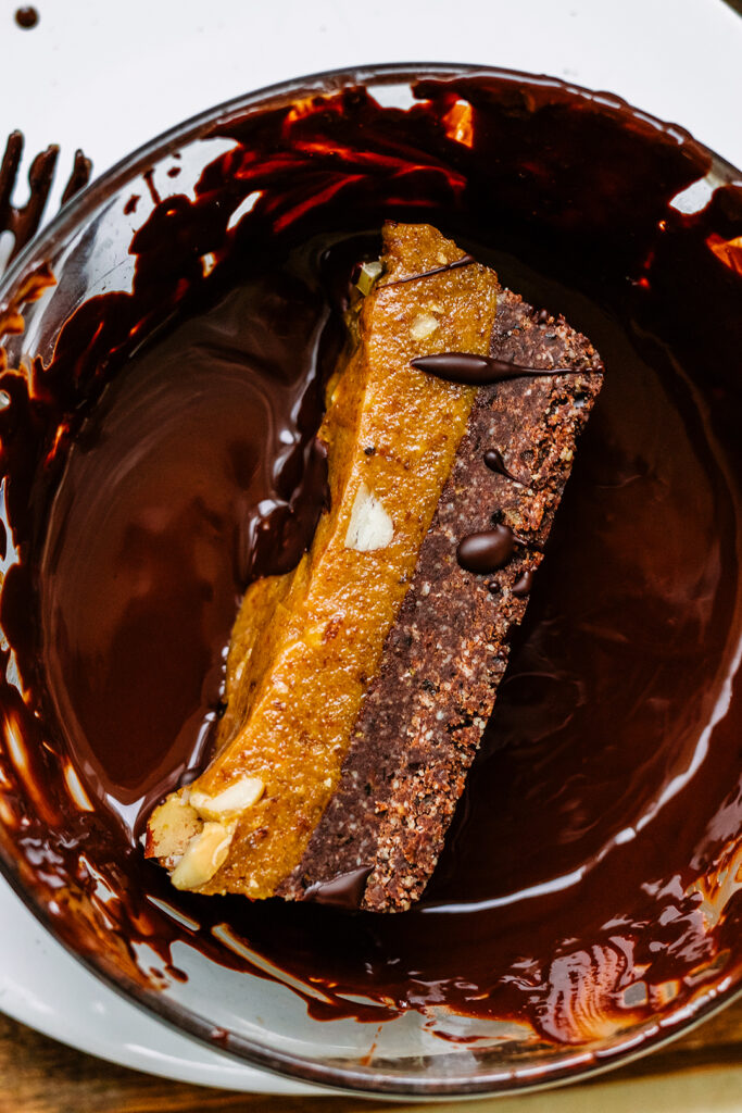 raw Caramel & Brazil nut chocolate bar in melted chocolate