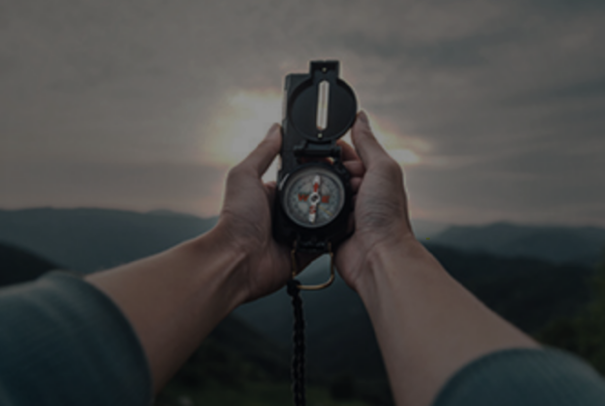 A man holding a stopwatch with a blurred landscape in the background