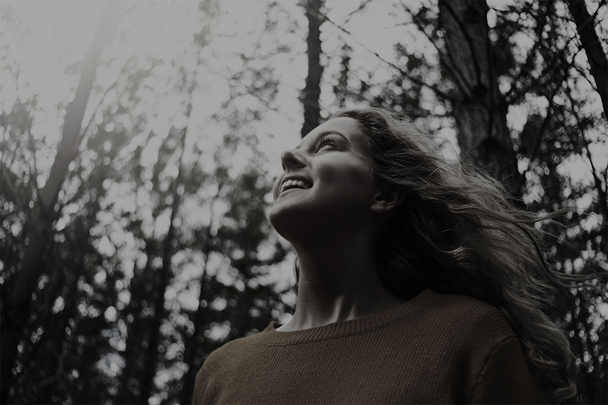 Low angle view of a smiling pretty blonde young woman looking up in the forest