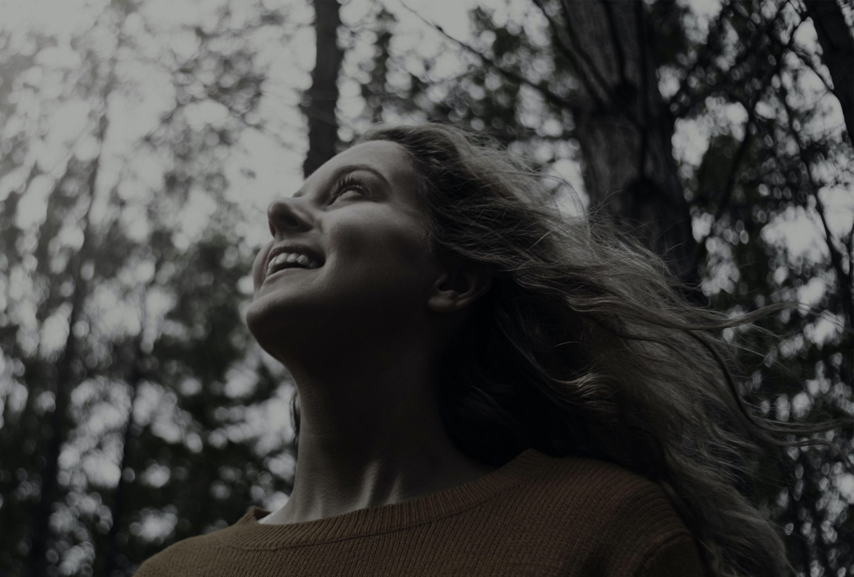 A woman walking in a wooded area with wind in her hair