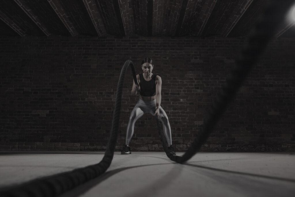 A woman exercising using batter ropes