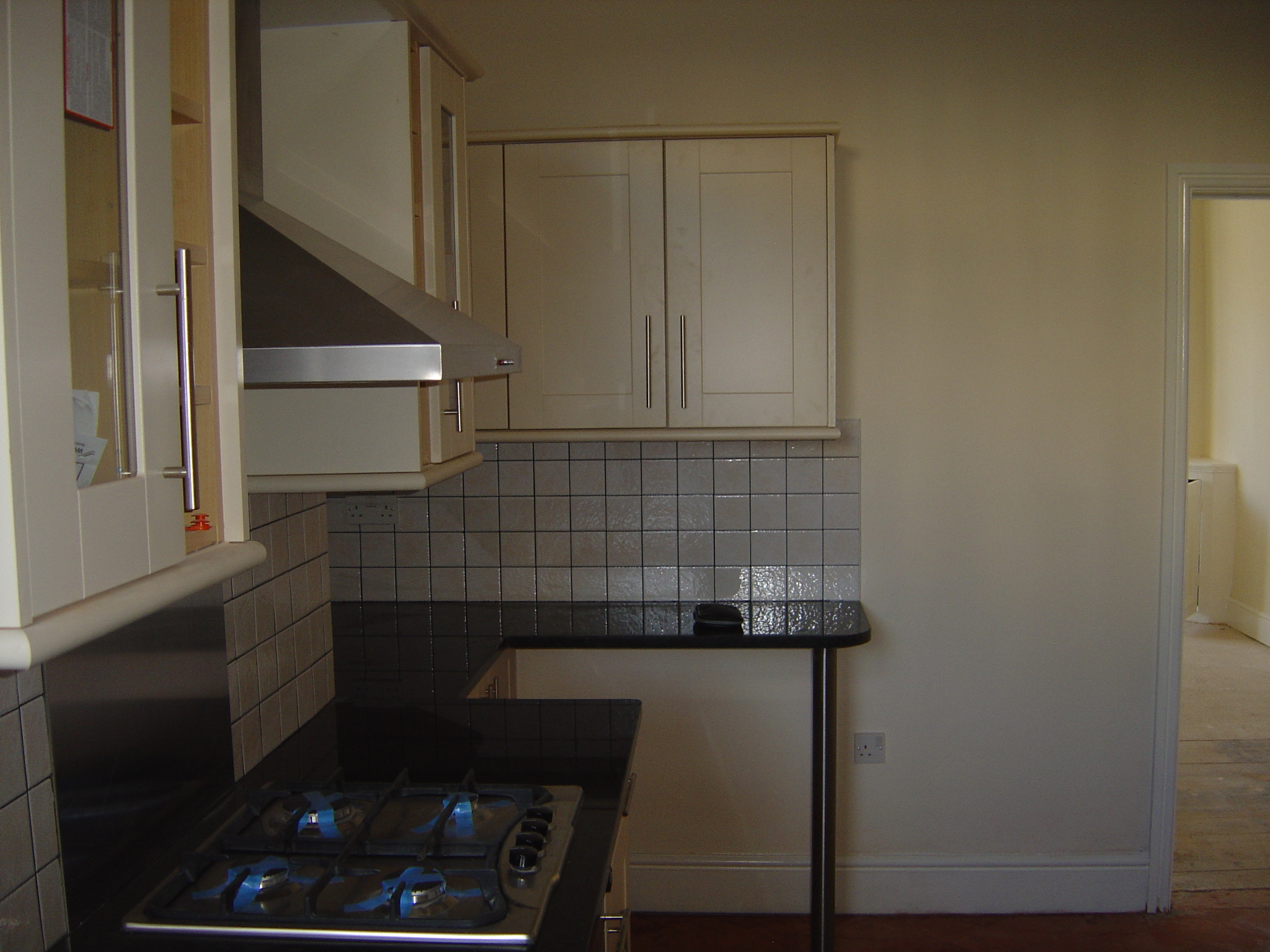 Kitchen with black granite worktops and brushed stainless splashback and black grout