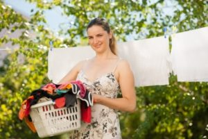 Young woman hanging laundry outdoors