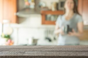 Blurred background with modern kitchen and woman preparing coffee