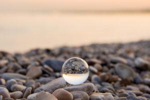 Glass marble on a pebbles beach