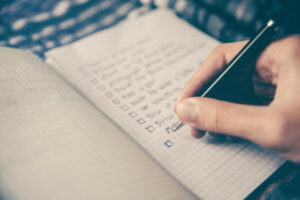 Writing a checklist in a notebook