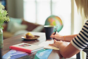Woman writing in a notebook with globe and cup of coffee in the background