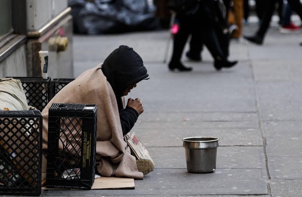 homeless man on street waiting for vaccine