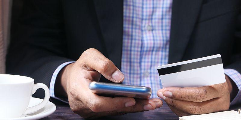 Uomo con carta di credito e cellulare in mano