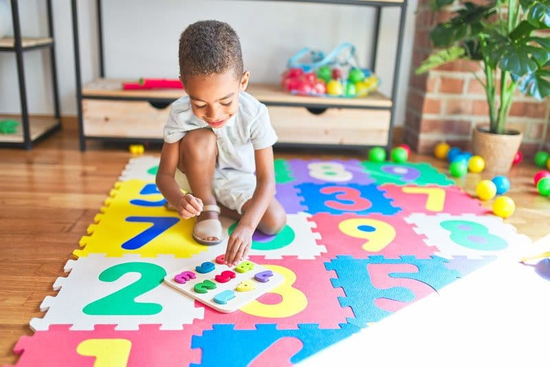 child playing with number mat