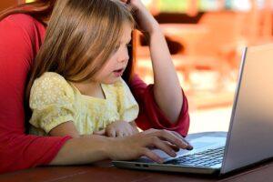 Girl on Mum's lap looking at a laptop - Raising Responsible Technology-Savvy Kids