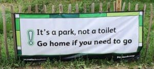 Example of sign present in many parks across City's in the UK that reads 'It's a park not a toilet, go home if you need to go'.