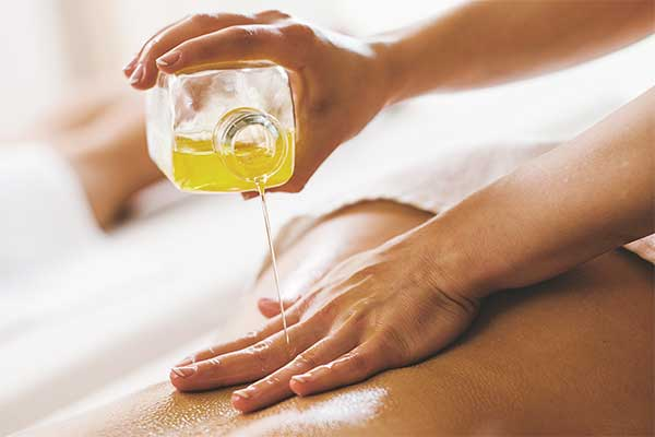 essential oil being poured on a woman's back, during an aromatherapy massage
