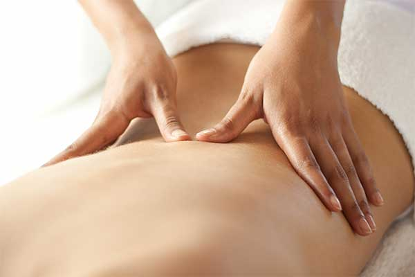 close-up of hands massaging a woman's back