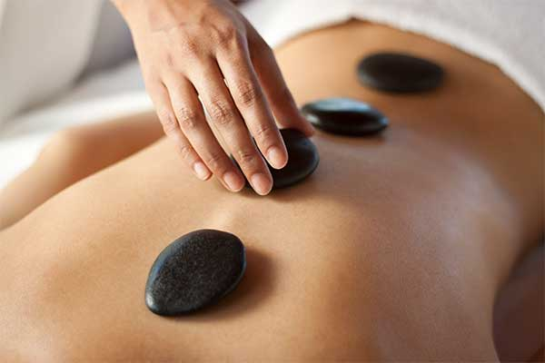 therapist placing a basalt stone on a woman's back, during a hot stone massage