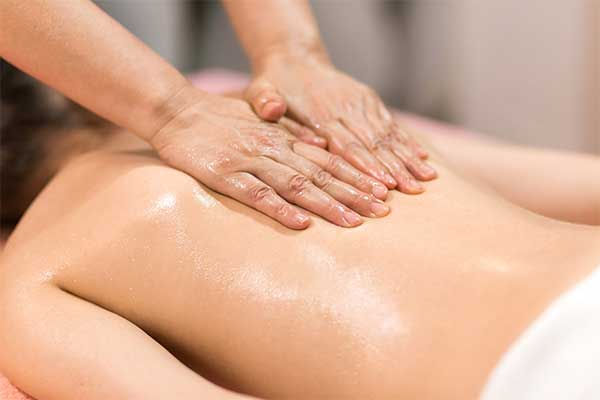 woman receiving an oil massage on her back