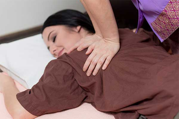 therapist applying Thai massage techniques, to a woman's shoulders