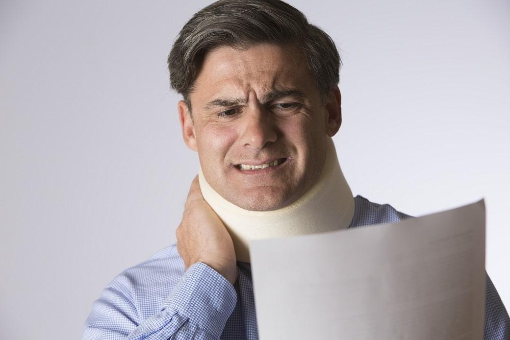 Studio Shot Of Man Wearing Neck Brace Reading Letter