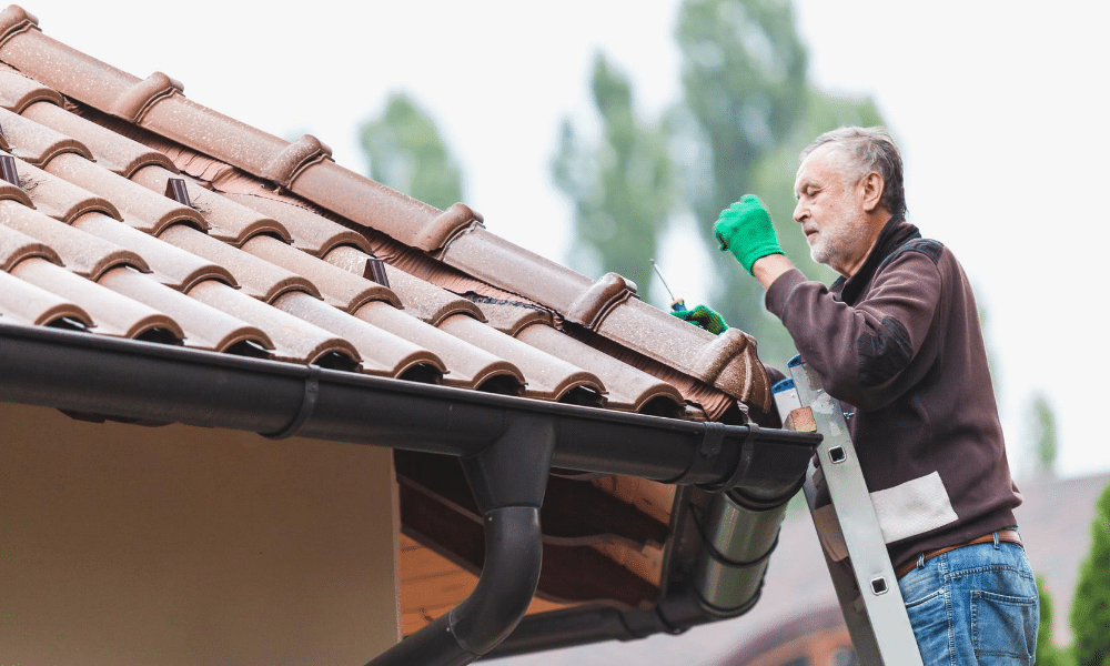 man on a ladder working on a roof