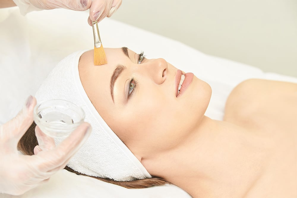 woman receiving chemical facial skin peel