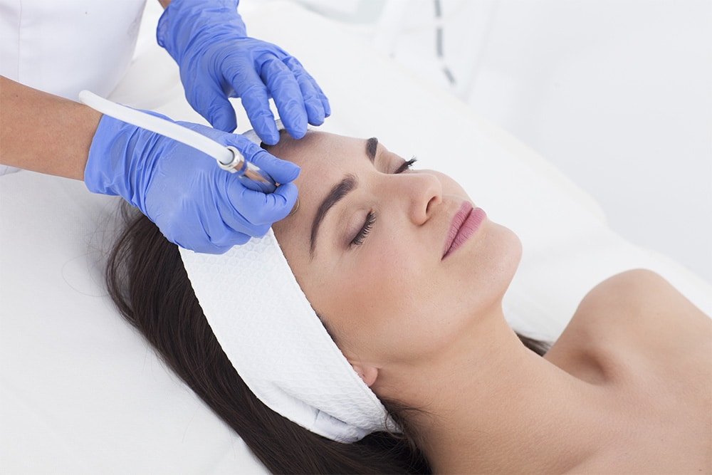 woman receiving microdermabrasion skincare procedure